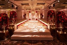elevated white aisle indoor jewish wedding ceremony, red roses