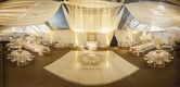 Tented wedding reception with white fabric, decor piece of strings of beads and sequins