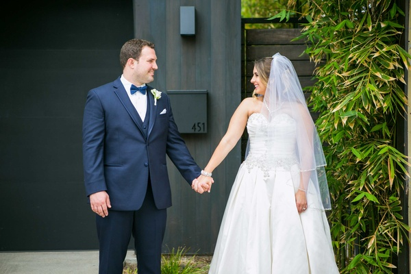bride in allure ball gown, groom in navy joseph abboud suit hold hands and gaze at each other