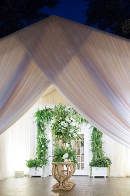 French doors decorated with greenery white flowers at entrance to tent reception venue drapery