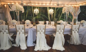 Wedding reception in Maui Hawaii jungle white linens draped from chairs pineapple decor white flower