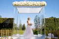 Bride in strapless wedding dress and white bouquet standing under lucite acrylic clear ceremony arch
