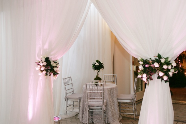 Table with silver linens and chairs if framed by white draping tied with red and white flowers