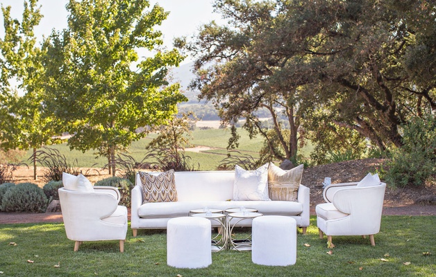 Outdoor wedding reception white sofa and armchair ottoman with collection of four side tables