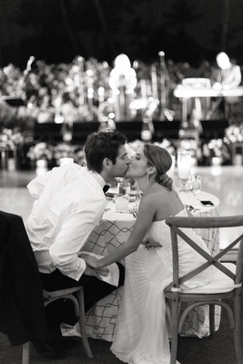 black and white photo of bride and groom kissing at their sweetheart table