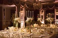 long tables with white linens and small floral arrangements with tall candelabra foliage flowers