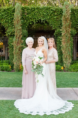 Bride in lace wedding dress with bouquet and mother of bride grandmother of bride grandma sparkly