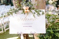 wedding ceremony welcome sign gold calligraphy eucalyptus peach rose flowers
