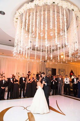Bride in strapless wedding dress and groom in tuxedo share first dance under flowers and crystals