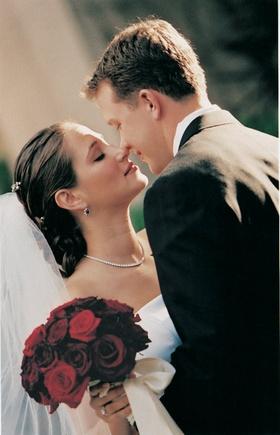 Bride eskimo kisses groom holding red flowers