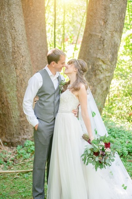 couple embrace each other gray suit white wedding dress celtic wedding green and red bouquet veil