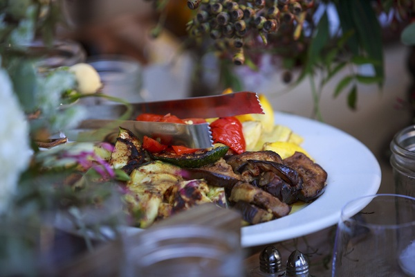 Rustic outdoor wedding reception table with a platter of grilled vegetables