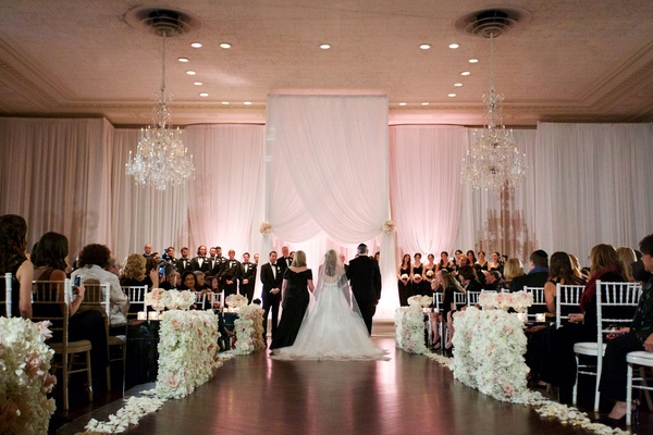 Bride walking down ballroom wedding ceremony aisle with mom and dad Jewish wedding tradition