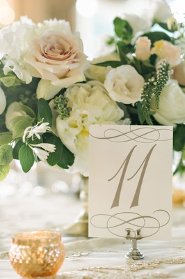 Wedding table number on linen with low flower arrangement pink rose ivory garden rose flowers