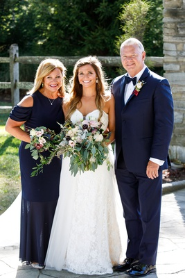 Bride in strapless lace wedding dress with rustic chic bouquet mother and father of bride in navy