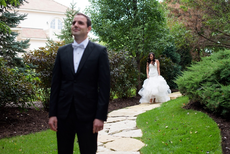 bride in monique lhuillier mermaid wedding dress walks up to groom in gibeon tolbert for first look