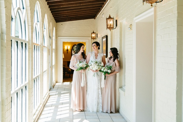 Bride and two bridesmaids in tan off shoulder dresses lace wedding dress ivory bouquets