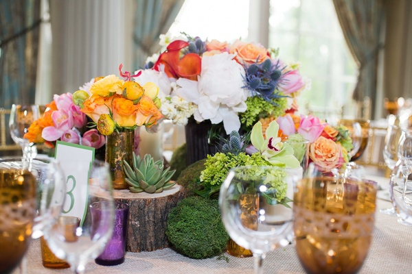 colorful rustic flowers and wood décor on table for gay wedding centerpiece