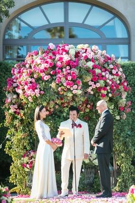 Vow renewal outdoor garden wedding with Las Vegas Elvis impersonator officiant bride in old dress