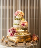 Round, swiss-dotted wedding cake with flowers