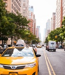 Driver in a yellow Toyota New York City taxi waves on downtown street