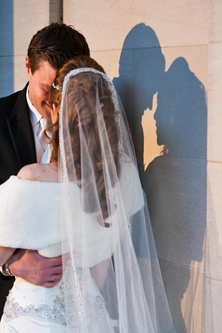 Bride in a stole and veil with groom in a black tuxedo