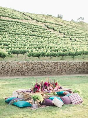 reception table pillow seats bold color scheme california boho chic wedding styled shoot vineyard