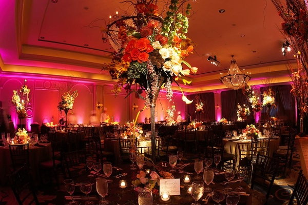Pink lighting at ballroom wedding with tall centerpieces