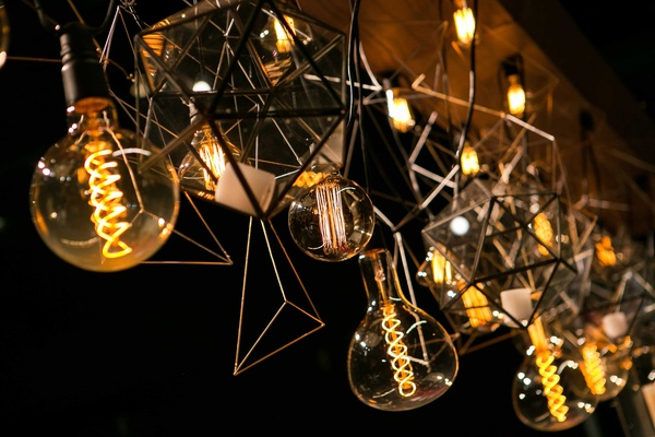 a unique lighting concept with hanging light bulbs and geometric shapes suspended from wooden board