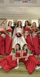 Bride with red bridesmaids on green staircase