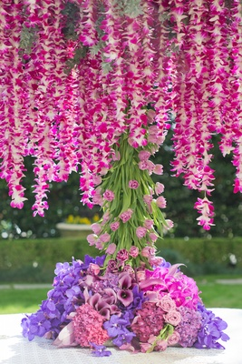 Wedding reception table with hot pink orchid garlands, trunk of pink tulips, purple orchids, roses