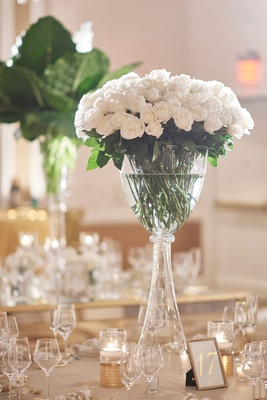 Round table with tall glass centerpiece long stem white roses gold candles table number