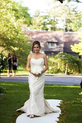 Bride walks down the aisle of an outdoor ceremony in a ruched Romona Keveza gown