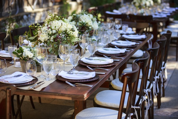 Ranch wedding reception table with beige runner, white roses, hydrangeas
