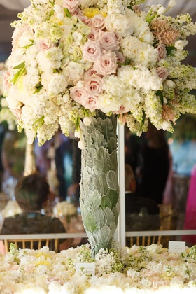 Wedding escort card table covered in flowers, vase covered in leaves with pink roses, white peonies