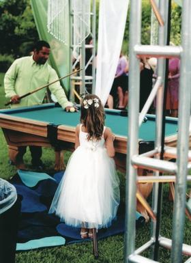 Flower girl watching guest play pool at custom blue suede pool tables