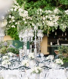 outdoor wedding reception with silver candelabra, white roses, black chairs