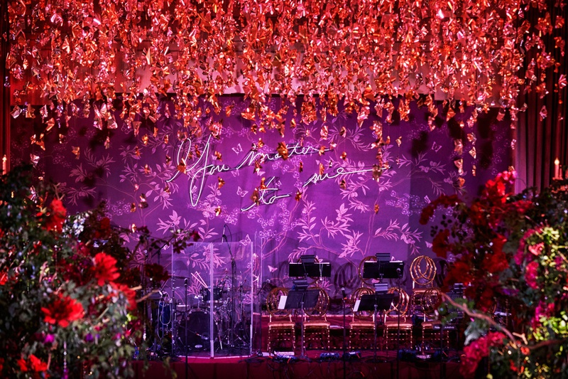 purple neon sign you matter to me red flowers hanging from ceiling over dance floor live band stage