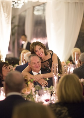 father of the bride sitting at table while the mother of the bride bends down to hug him from behind
