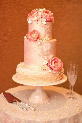 Wedding cake with two pink layers and gold finish, off-white ruffled layer, pink sugar peonies