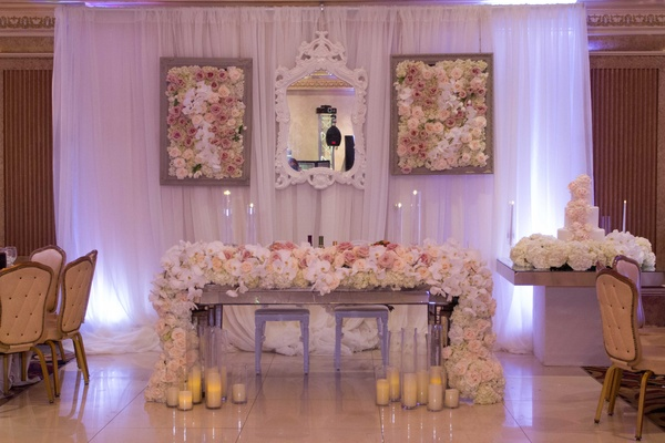 Sweetheart table at ballroom Armenian reception with lush flower overflowing runner, flower panel