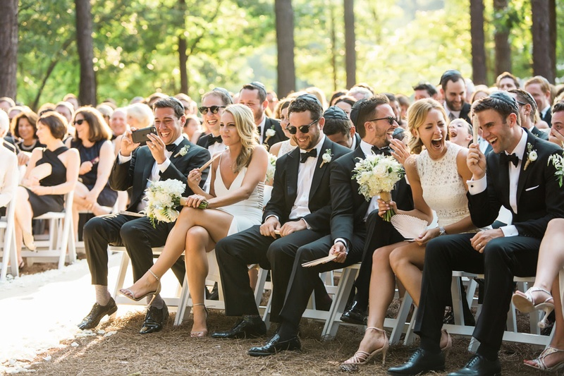 Bridesmaids and groomsmen sitting in front row white dresses outdoor wedding laughing guests smiling