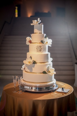 White cake with gold ribbons, monogram, and magnolia sugar flower