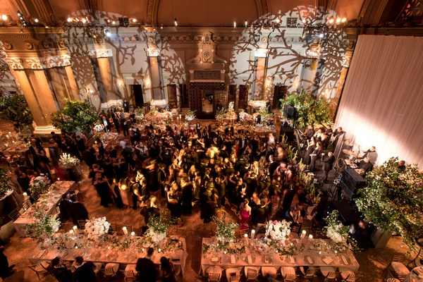 Wedding reception light projections on wall tree branch designs flowers guests on dance floor