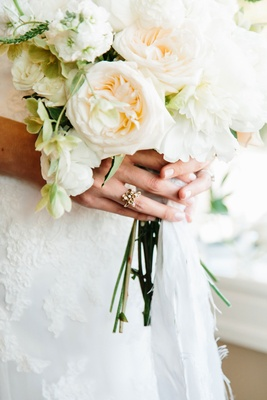 White garden rose bouquet being held by bride in vintage inspired gold engagement ring