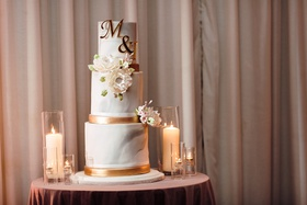 Three-tier wedding cake with marble frosting and copper accents