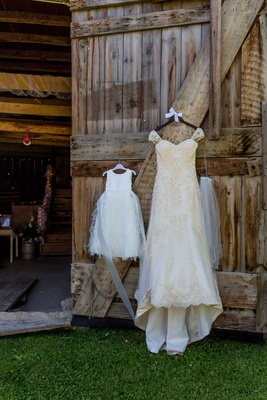 Ivory Maggie Sottero wedding dress hanging on barn door with flower girl dress
