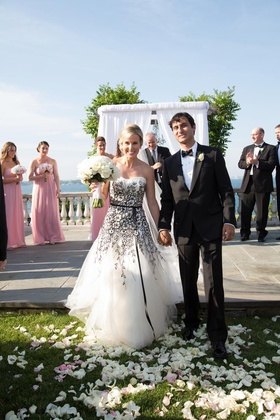 Bride and groom hold hands at outdoor ceremony altar