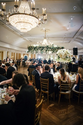 Sophisticated ballroom wedding reception crystal chandelier greenery wreath over dance floor