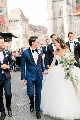 wedding in germany bride and groom walking with wedding party family down streets of german town